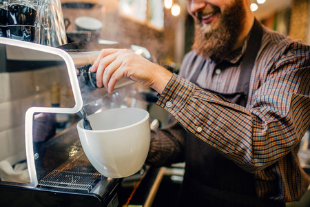 Picture of young barista pouring some coffee into huge white cup. He does it with smile and pleasure. Guy stand at coffee machine in kitchen.