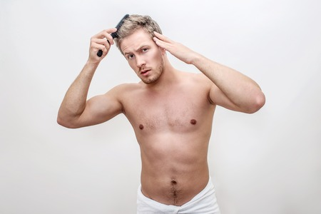 Worried young man look on camer and brush his hair. Guy touch it. He has problem. His hips are covered with towel. Isolated on white background.