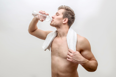 Side shot of young well-built man drinking water. He hold white towel around neck. Isolated on white background.