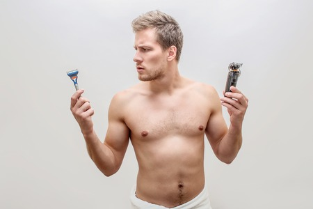 Well-buil and muscular young man hold razers and shving machine in both hands. He looks at first device. Guy is shirtless. Isolated on white background. Stock Photo