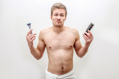 Baffled young man hold razers and shaving machine in hands. He looks on camera. Guy is shirtless. Isolated on white background.