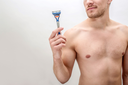 Cut view of young man holding razers in hand. He smiles. Guy is shirtless. Isolated on white background.