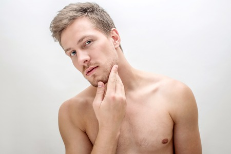 Handsome young man looking straight. He touches face. Guy is shirtless. Isolated on white background.