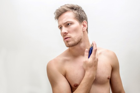 Picture of young shirtless man spraying some perfume. He hold bottle of it close to neck. Isolated on white background. Stock Photo