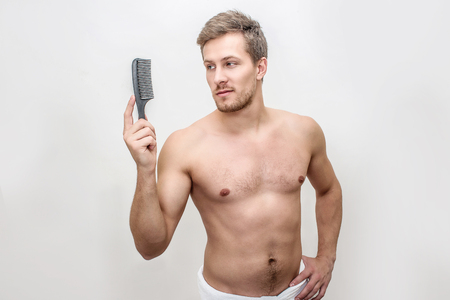 Handsome young man hold brush in hands. He looks a it. Guy is shirtless. He wears towel around hips. Isolated on white background.