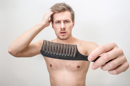 Worried young londe man look at brush. He hold it on left hand. Right one is on hair. Guy is shirtless. Isolated on white background. Stock Photo