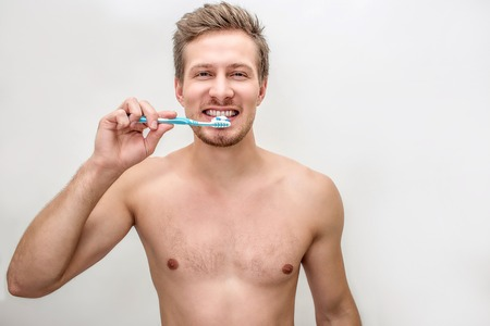 Well-built and shirtless young man cleaning his teeth with toothbrush and toothpaste. He looks on camera. Isolated on white background.