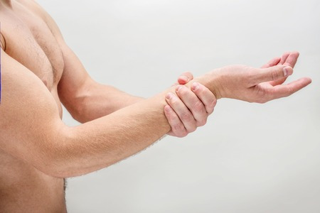 Side shot of young man hold hand on wrist. He is shirtless. Isolated on white background.