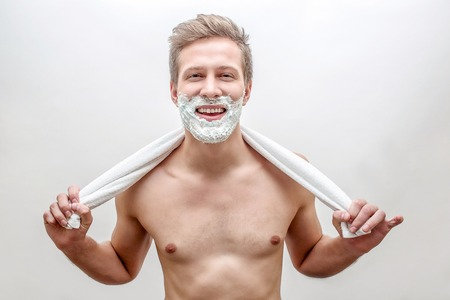 Happy young man with foam on beard look straight. He hold towel in hands behind neck. Guy smiling. Isolated on white background.