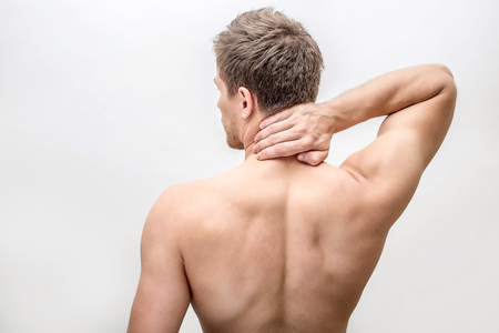 Shirtless young man stand and hold hand on neck. He feels pain there. Guy shows his back. Isolated on white background.