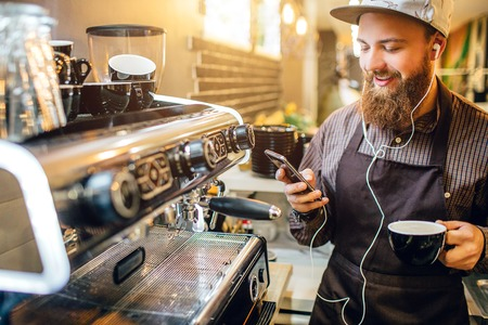 Positive young barista listen to music through headphones. He looks at phone he holds in one hand. In other is cup of coffee. Stock Photo