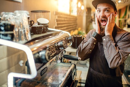 Scared young barista looks on camera. He holds both hands on cheeks. Guy stand at coffee machine. He is terrified. Stock Photo