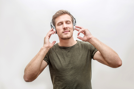 Young man enjoying listening to music. He hold hands on headphones and keep eyes closed. Isolated on white background.