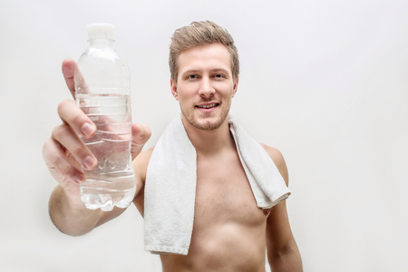 Handsome shirtless oyung man hold glass of water. He shows it on camera. Guy has towel around neck. Isolated on white background.
