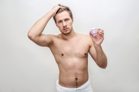 Young male model hold one hand on hair. He poses on camera. Face cream is in another hand. Isolated on white background.