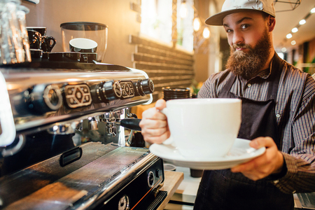 Young bearded barista holding huge white cup of coffee in hands. He looks on camera and smiles. Guy stand in kichen at coffee machine.