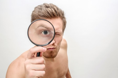 Suspicious young man look straight with one eye using magnifying glass. He hold it in right hand. Isolated on white background.