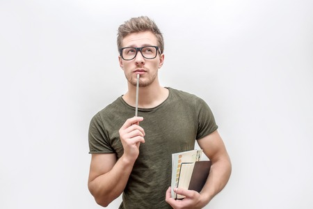 Young man in green shirt hold books and pencil in hands. He looks on camera through glasses. Isolated on white background.