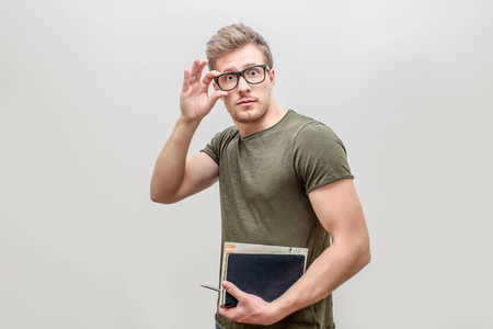 Well-build and strong young man posing on camera. He looks straight and hold hand on glasses. Guy has books in other hand. Isolated on white background. Stok Fotoğraf