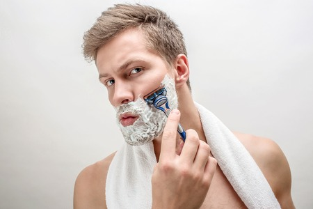 Portrait of young man shaving. He has white foam on beard. Guy is serious and concentrated. Isolated on white background.