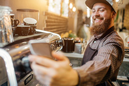 Positive young barisa taking selfie on workplace. He standi n kitchen at coffee machine. Guy is happy. Stock Photo