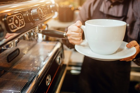 Cut view of barista holding huge white cup of coffee in hands. He stands in kitchen at coffee machine. Stock Photo