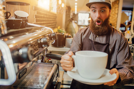 Amazed young bearded man hold huge white coffee cup in hands. He looks at it with excitement. Guy stand at coffee machine in kitchen.