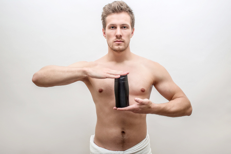 Serious young man look straight. He hold black bottle of shampoo in hands. Guy is shirtless. Towel around hips. Isolated on white background.