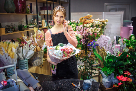 Busy young florist hold bouquet in hand. She talk on phone. Young woman stand in room full of flowers and plants.