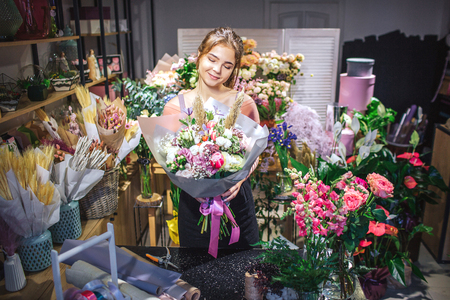 Nice and attractive florist is among colorful flowers. She hold bouqette in hands and look at it. Young woman smiles.