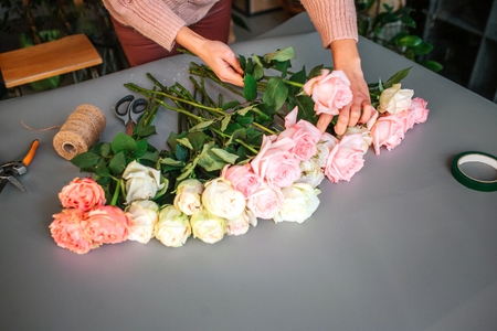 Picture of womans hands putting roses together on grey table. Coil thread lying there with nippers and scissors.