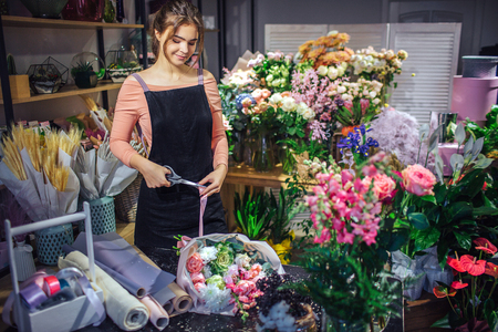 Nice oung woman stand in room full of flowers and plants. She look down and cut violet ribbon. It it tight to bouquet on table.