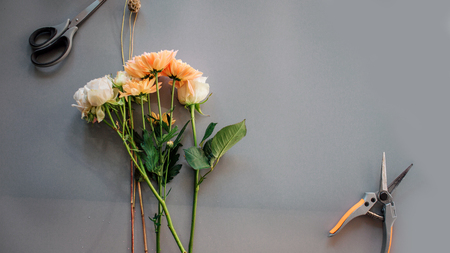 White roses and orange chamomile lying together in one bouquet on grey background. There are scissors and nippers.