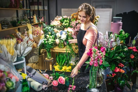 Young female florist taking rose from table. She create bouquet. Young woman look down. She is surrounded with flowers and plants. 版權商用圖片