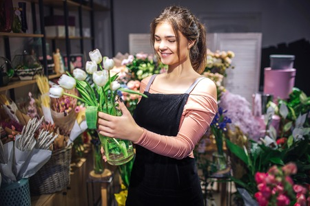 Cheerful young woman hold glass flower vase with white tulips. She smiles. Florist stand in flower shop. Stok Fotoğraf - 114828536