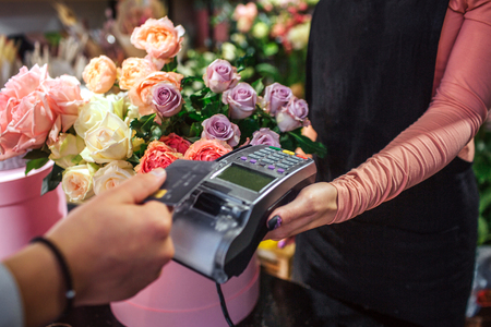 Cut view of man holding credit card above money therminal. He pays for flowers. Young female florist hold money therminal. Lots of flowers are behind her. Stock Photo