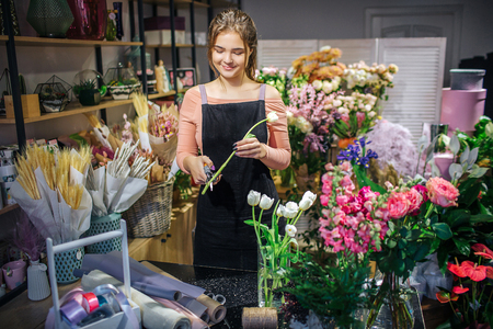 Cheerful young female florist stand in flower shop. She hold white tulip and cut part of stalk. She smile.