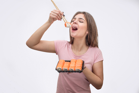 Cheerful young woman put piece of roll into mouth. She use shopsticks. Isolated on white background.