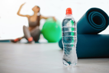 Water bottle stand at man in sport room. Young woman sit behind close to fitball and srink water. She is in bright room have rest Banque d'images - 119518376