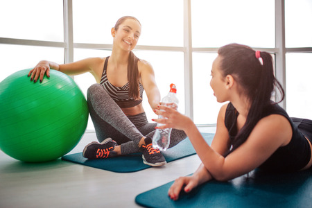 Two young friends sitting and lying on matrass. They talks and have rest after workout. Asian model hold water bottle. European woman lean on green fitball