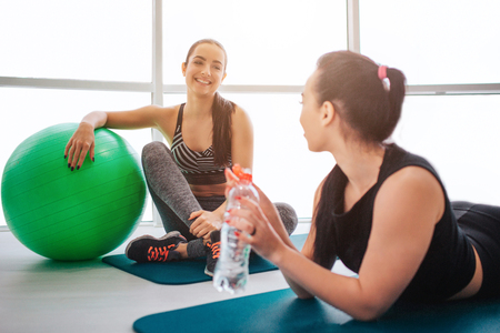 Two young women sit and lying on mattress in fitness room. They talk and have fun. Models have rest after workout. European young woman lean on green fitball