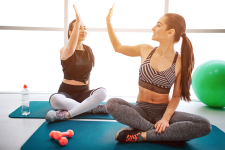 Happy young women sit on mattress and give high-five to each other. Models smile. They have rest in fitness room after workout