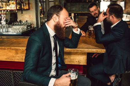 Tired young man sit and cover face with hand. Two other men sit behind and talk. They are in bar.