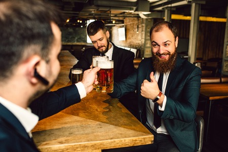 Cheerful young businessmen sit at table. They hold mugs of bear. Bearded guy hold big thumb up