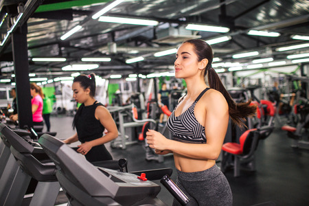 Nice young woman runs on running machine. She looks concentrated. Young asian woman runs as well further. They in gym room alone
