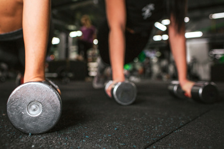 Cut view of two pair young women's hands standing on dumbbells. They work together on same floor in gym