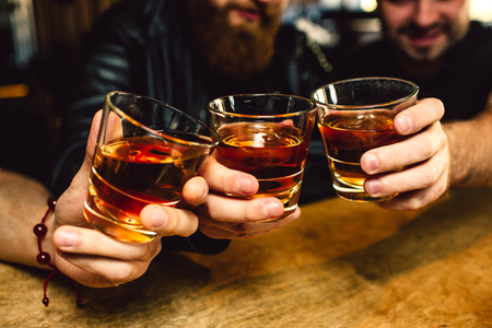 Cut view of three bearded young men holding glasses with rum together. They smile. People sit in bar 스톡 콘텐츠