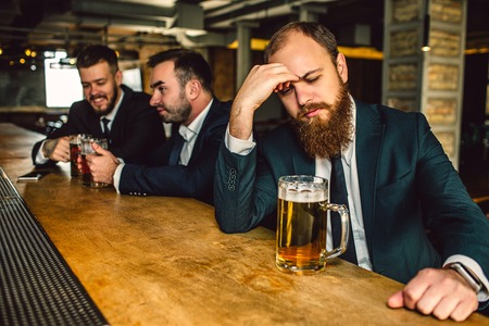 Upset and tired young man sit t bar counter. He look down and hold hand on forehead. Mug beer stand on bar counter. Other two young men sit behind.