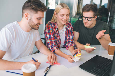 Picture of three coworkers sitting together at table in room. Young woman hold color palette and look at it. One guy white on paper. Another discuss.