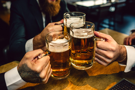 Three man in suits hold mugs of beer together. They sit at table. 写真素材